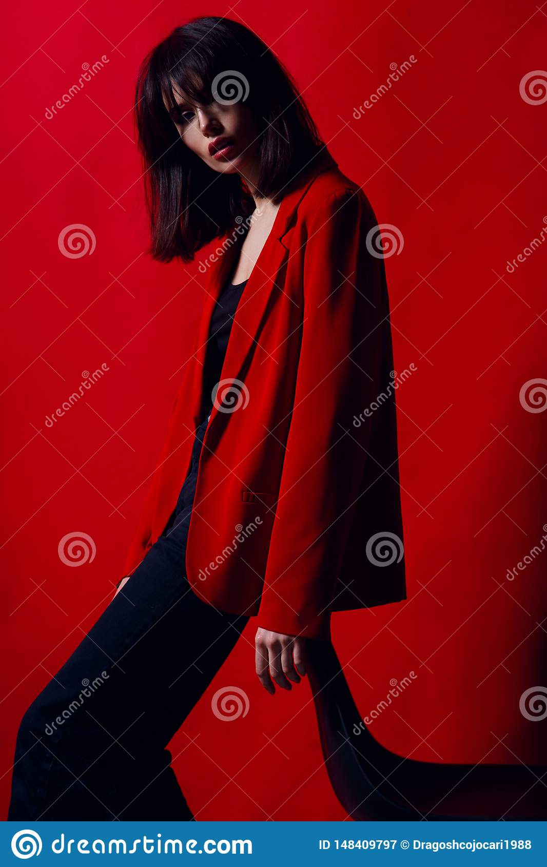 Portrait of a young woman in profile, posing in studio standing on chair in red suit, on a red background.