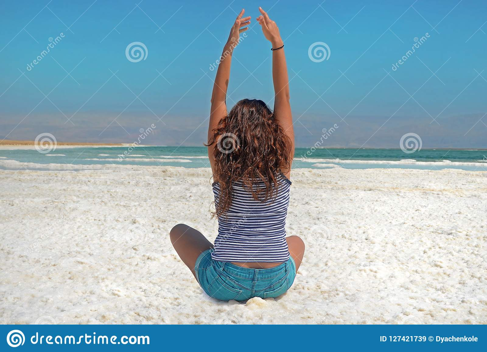 The brunette stretches her arms up, looking at the mountains of Jordan