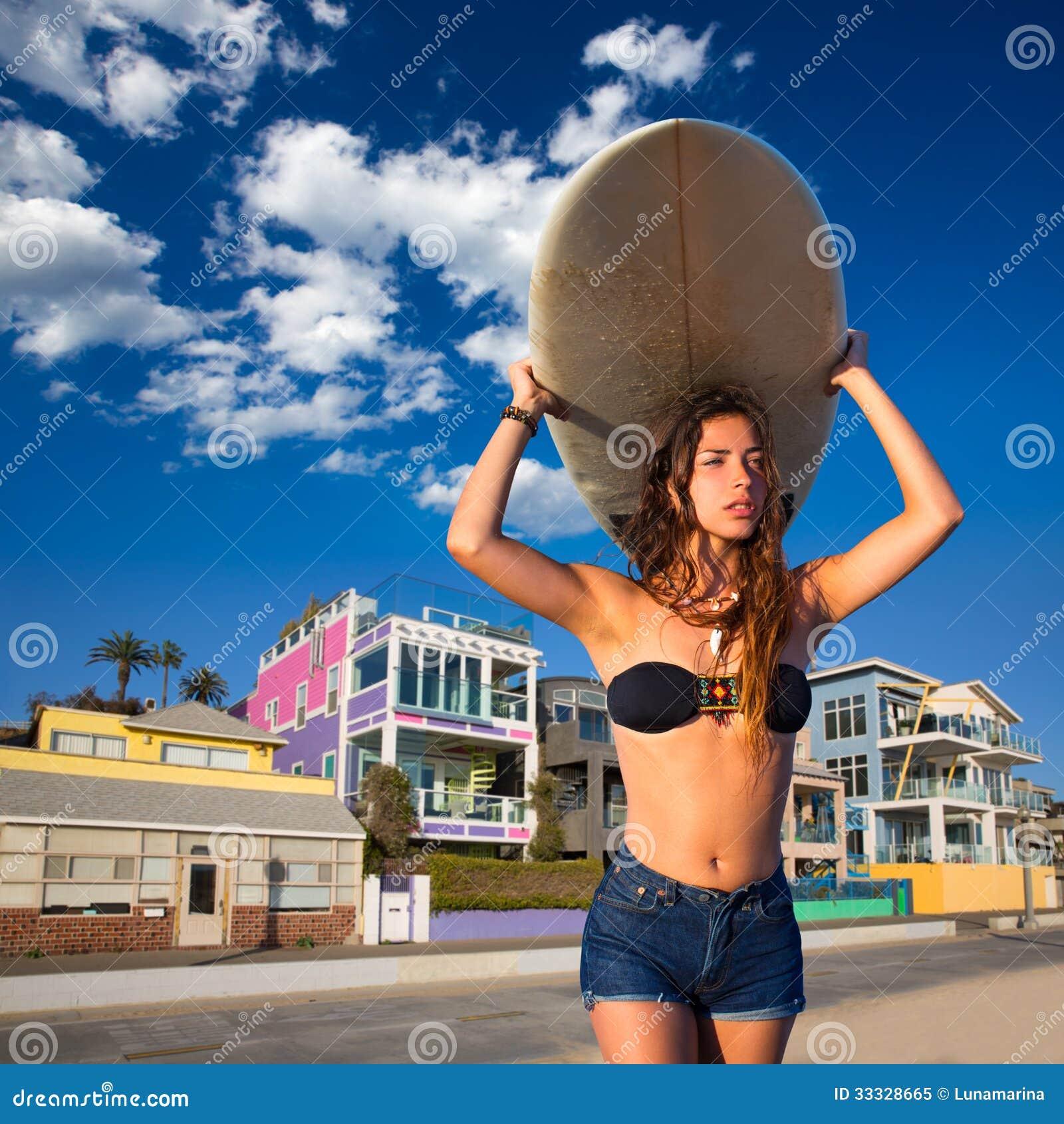Brunette surfer teen girl holding surfboard in a beach