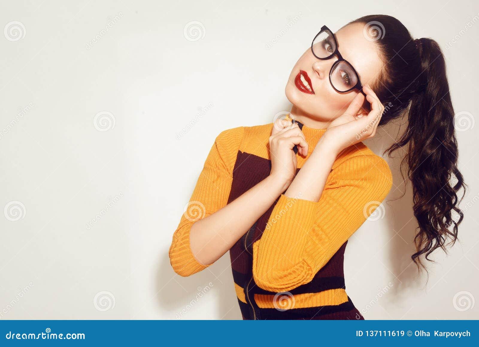 Brunette vorbildliches Mädchen der Schönheits-Mode, das stilvolle Gläser trägt Sexy Frau mit perfektem Make-up, modischem orange