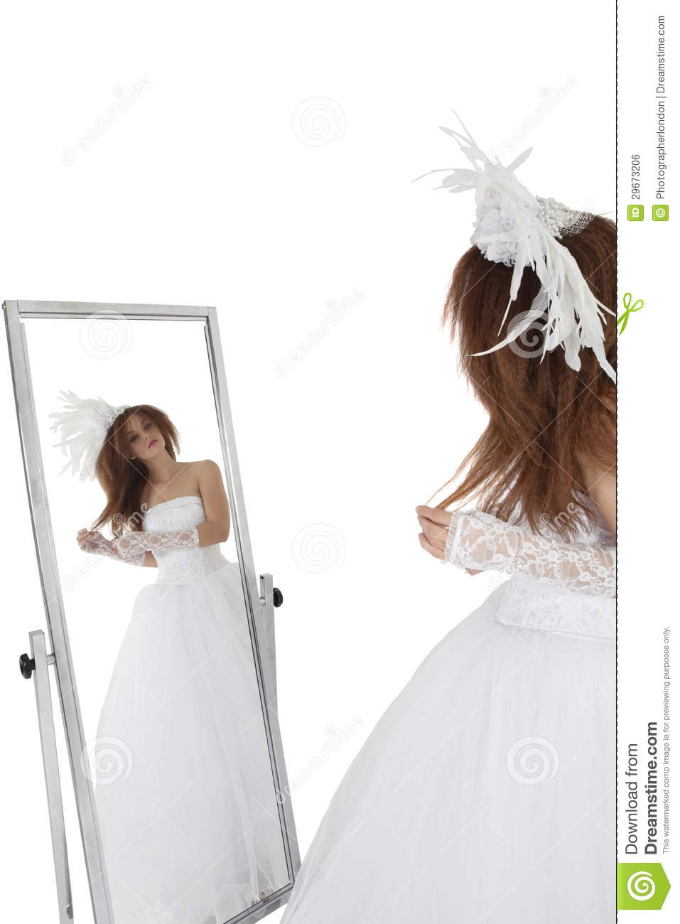 Brunette In Wedding Gown Looking At Mirror Over White Background Royalty Free Stock Image