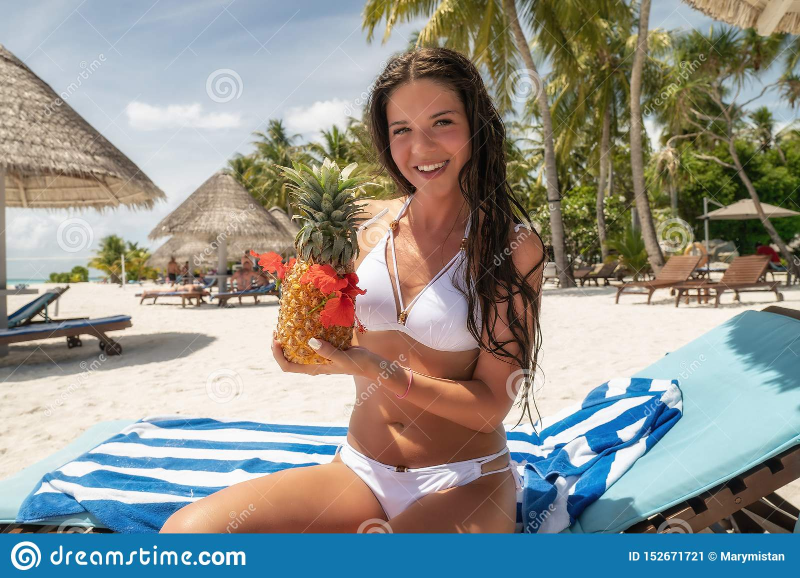 A brunette in a white bathing suit sits on a lounger with a Pina Colada cocktail in a pineapple
