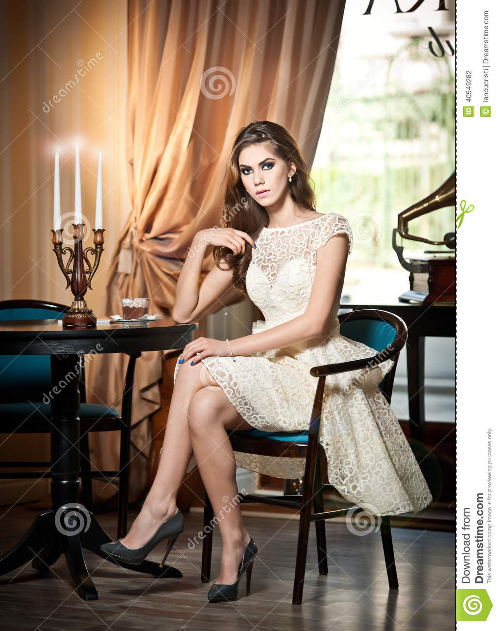 Brunette Woman In Elegant Lace Dress Sitting Near A Table