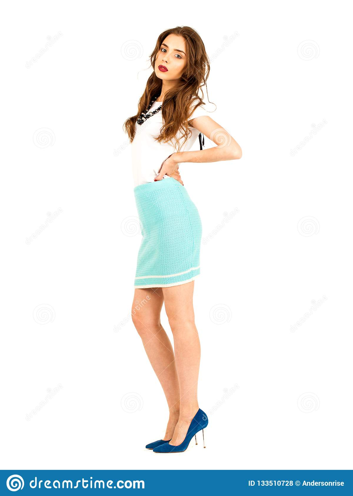 Brunette woman in a knitted turquoise skirt and white t-shirt