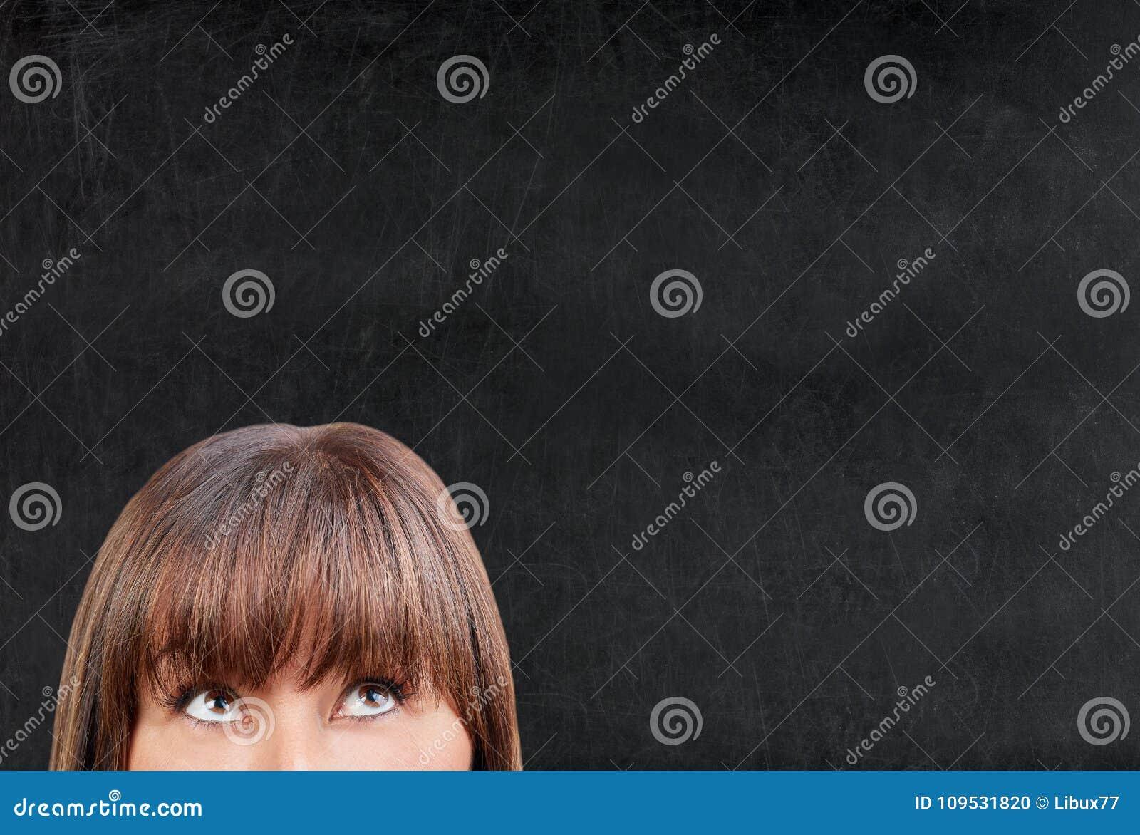 Brunette woman looking upward against blank blackboard chalkboar