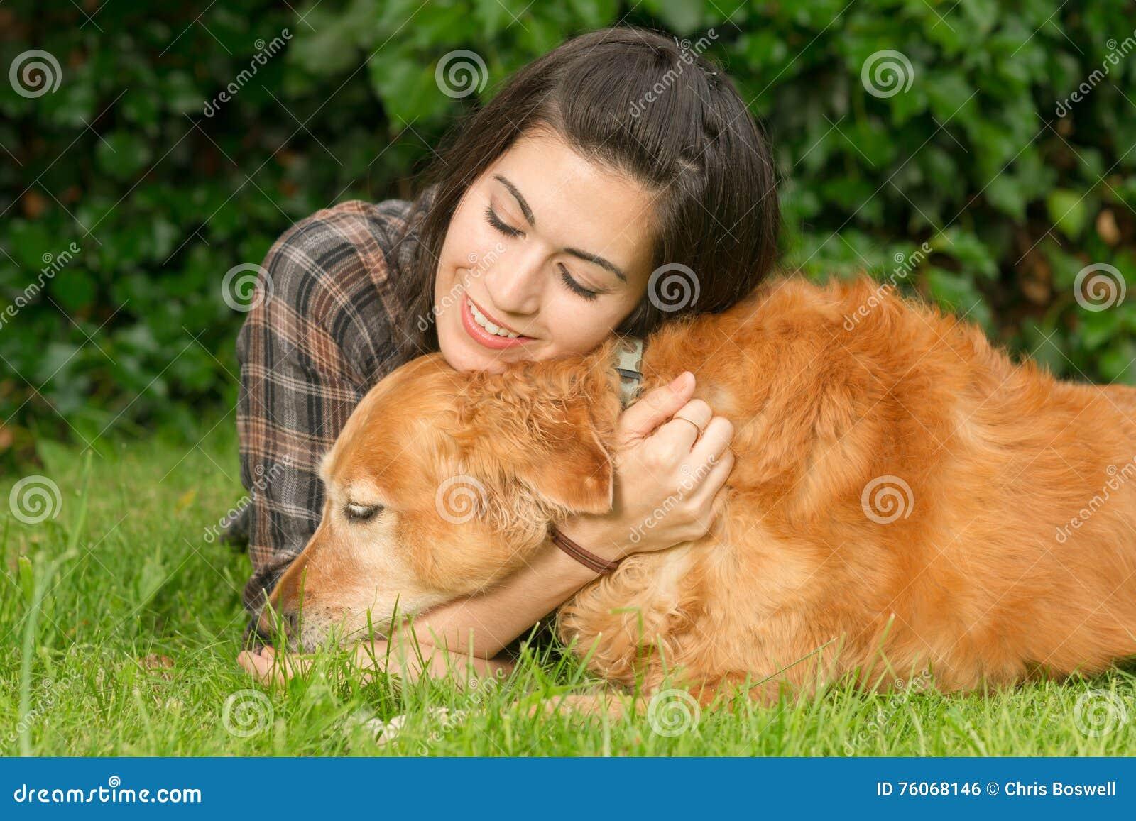 brunette woman praising her golden retriever dog canine stock photo