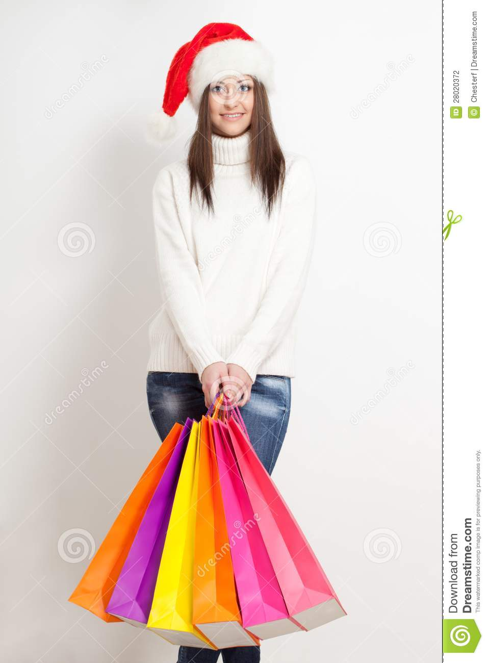 5d8fba2eb9ff0 Happy smiling brunette woman in santa hat holding color shopping bags