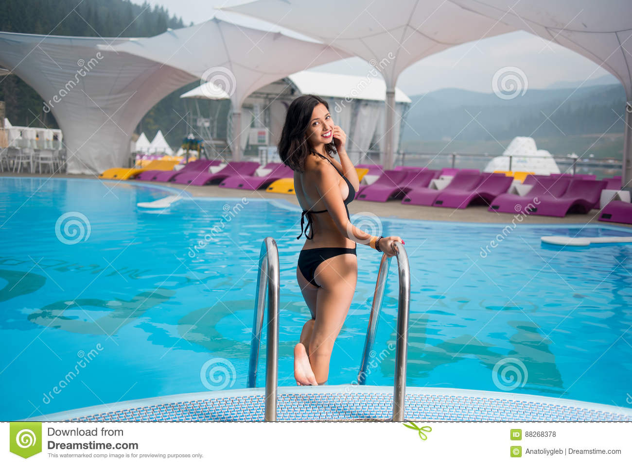 a4d8304d1e0b8 Brunette woman in a black bikini near swimming pool and turning back to  smile at the camera on mountain resort against the backdrop of the mighty  forest and ...