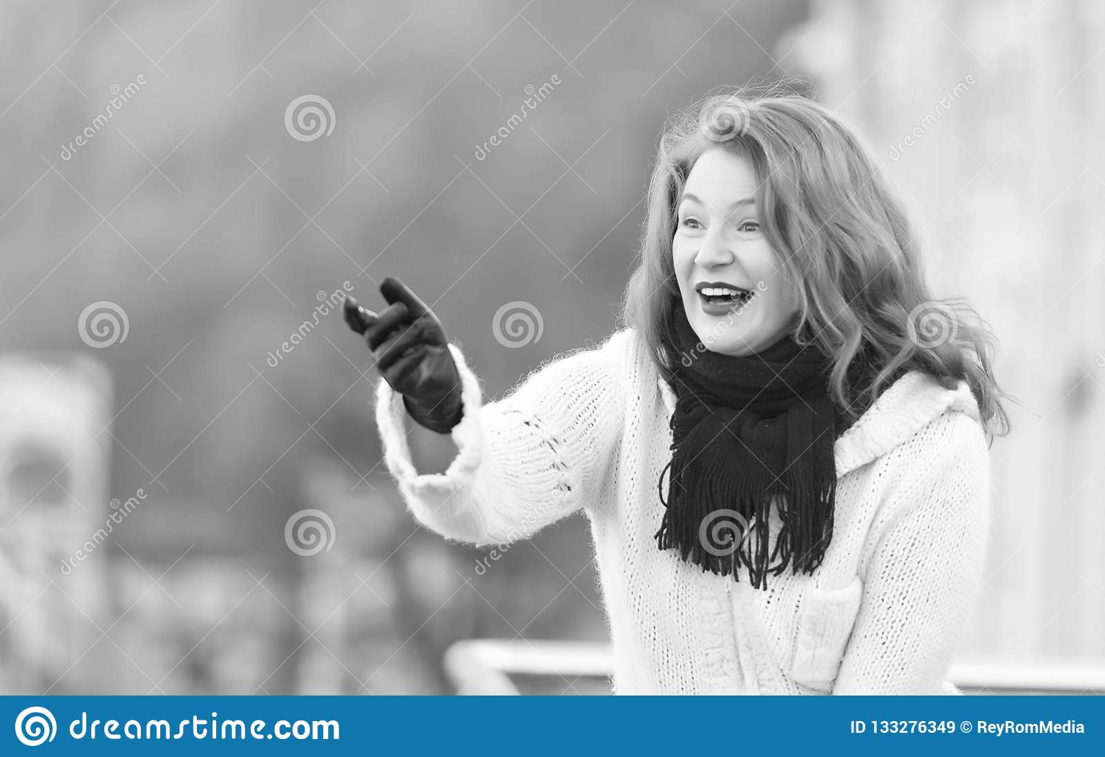 Attractive lady in white knitted coat and scurf. woman exited welcome on street.
