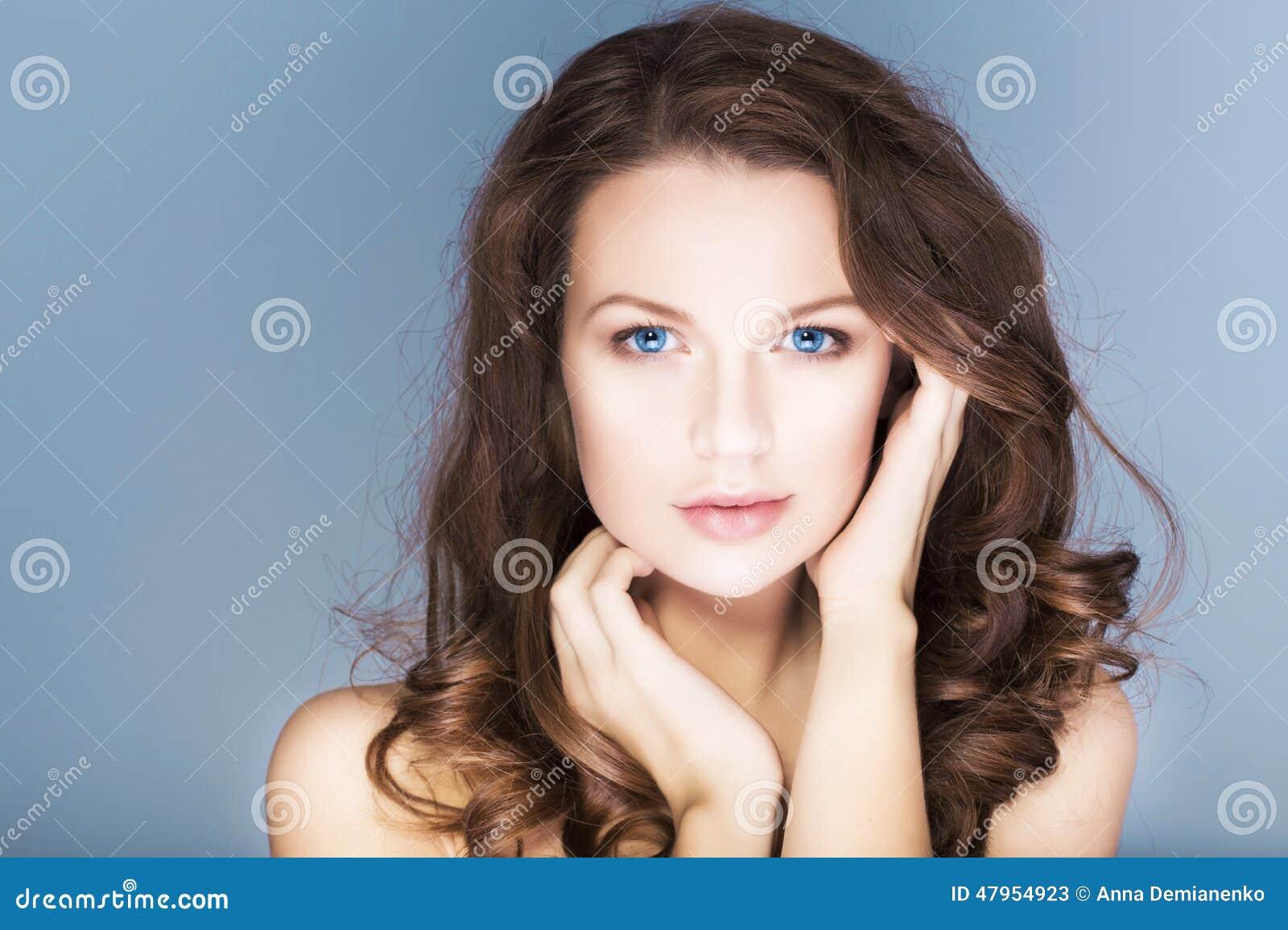 Brunettefrau mit blauen Augen außen bilden, natürliche makellose Haut und Hände nahe ihrem Gesicht