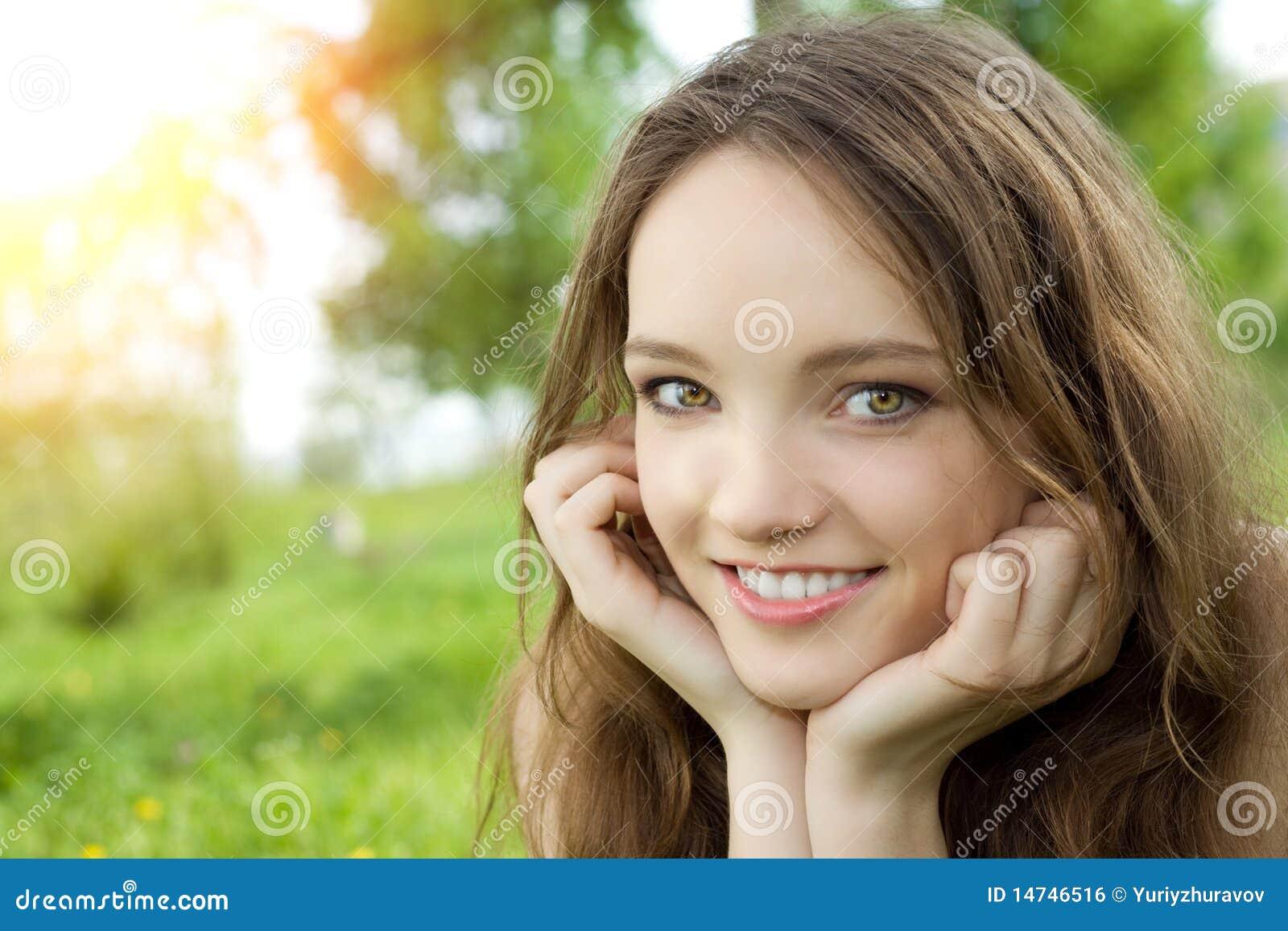 Brunettejugendlich-Mädchenlächeln auf Wiese