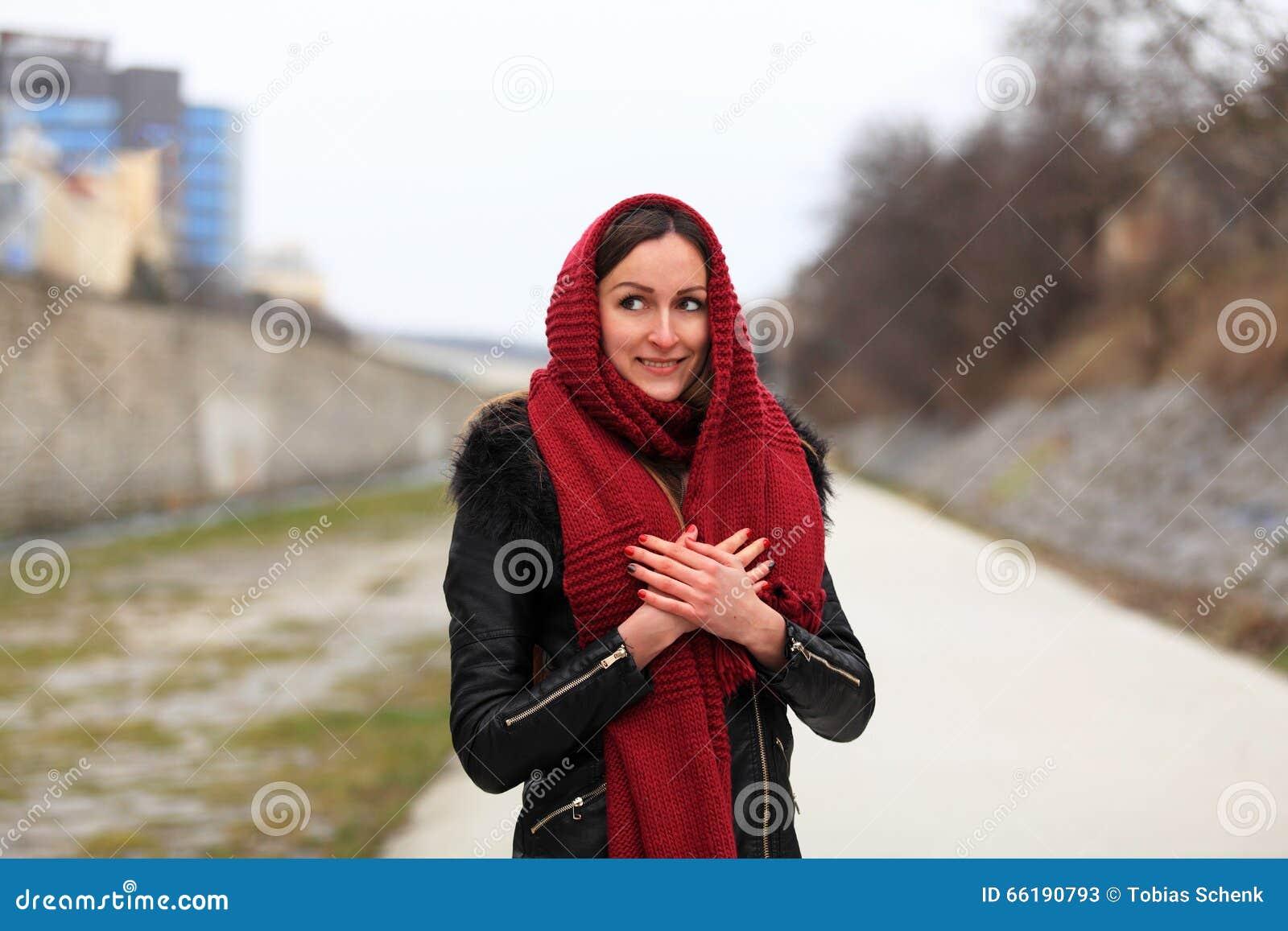 Brunettemädchen, das schwarze Lederjacke mit einem roten Schal trägt