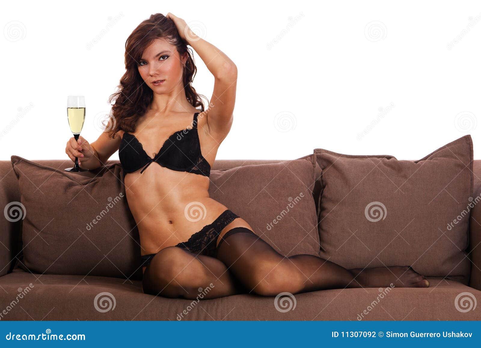Brunettemädchen in der schwarzen Unterwäsche, die auf ein Sofa legt