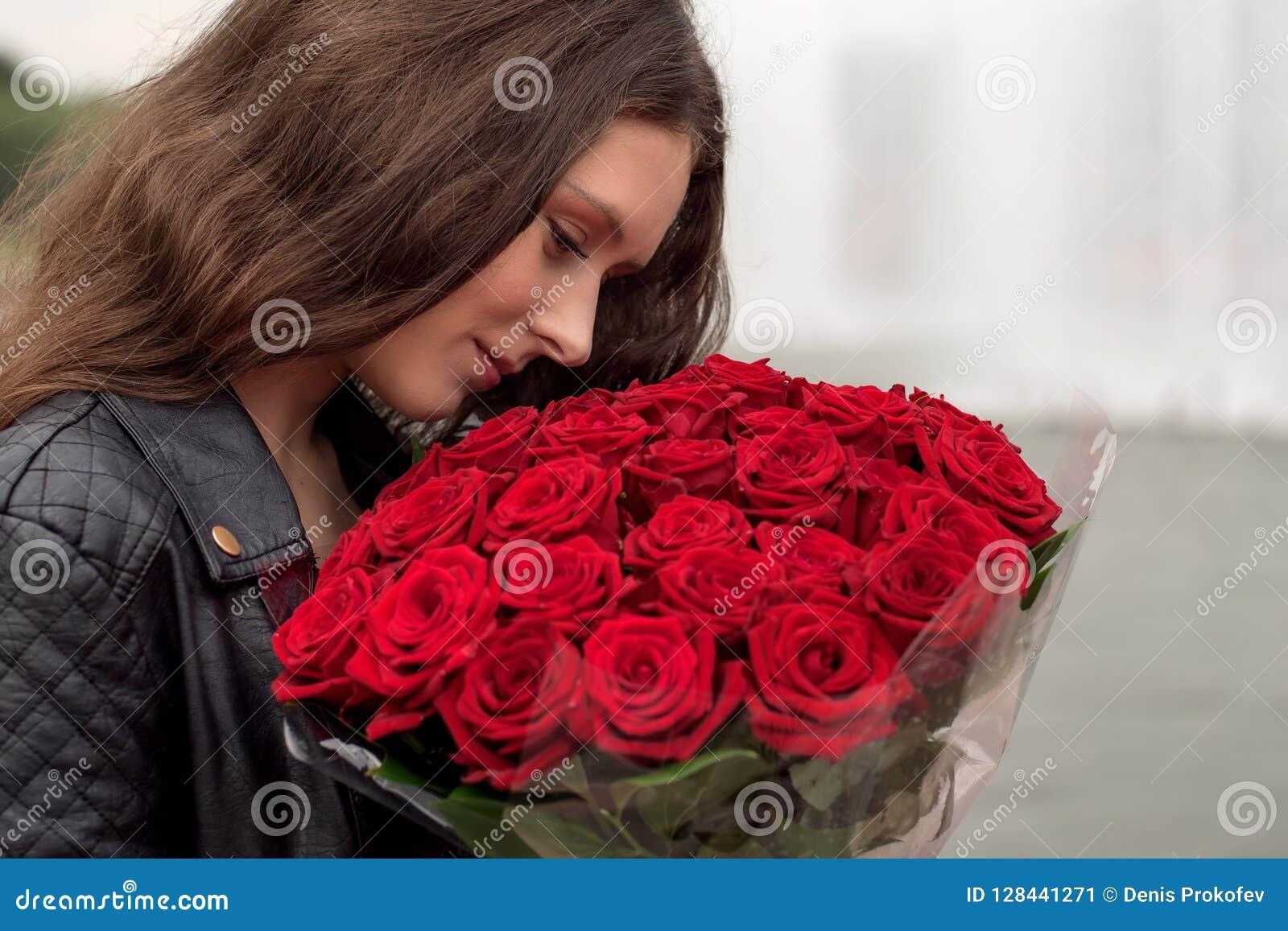 Brunettflicka med en bukett av röda rosor
