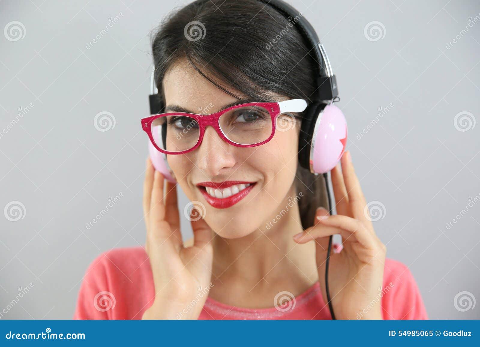 Brunettflicka med glasögon som lyssnar till musik