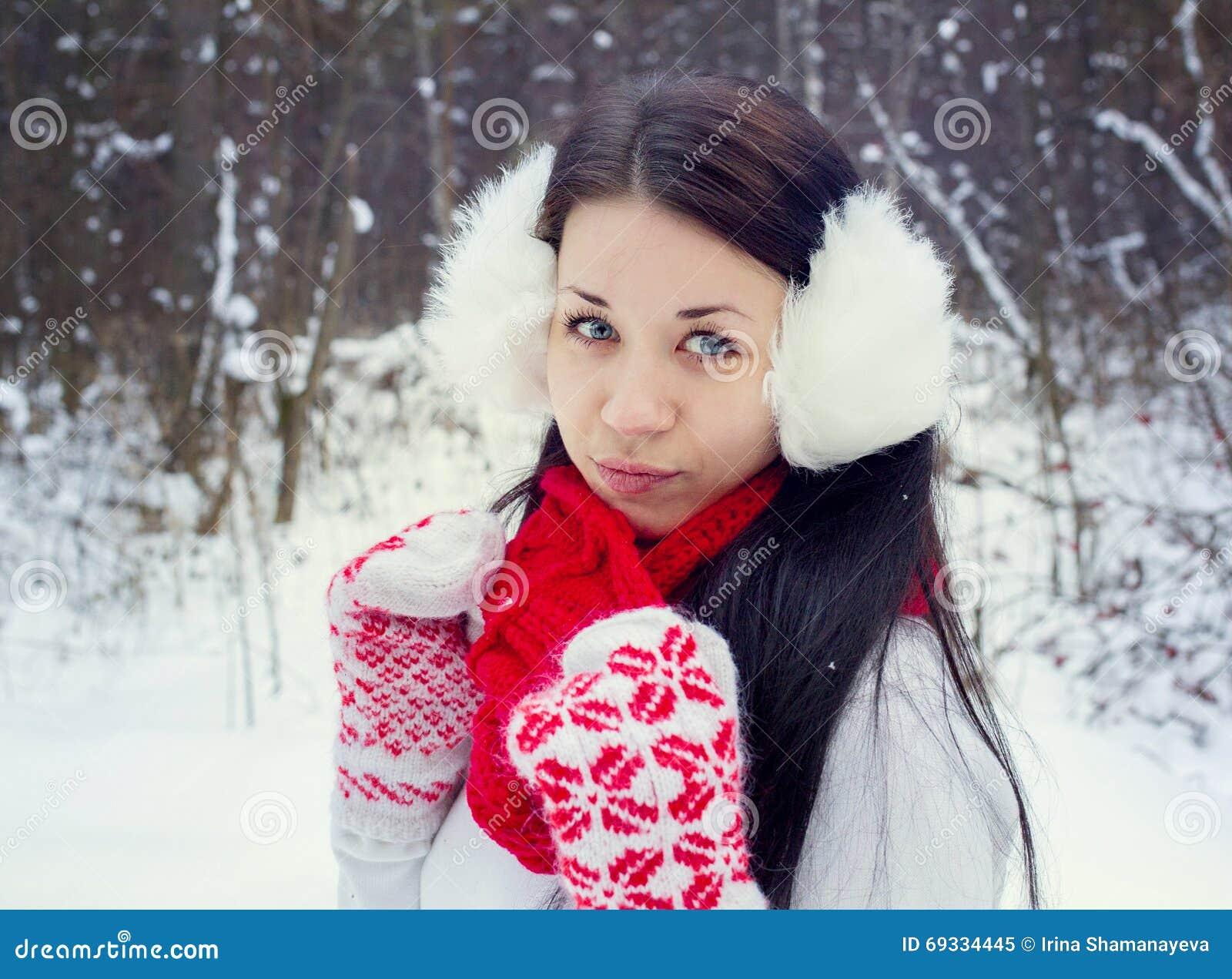 Brunettflickan i hatt och tumvanten hugger en snögubbe