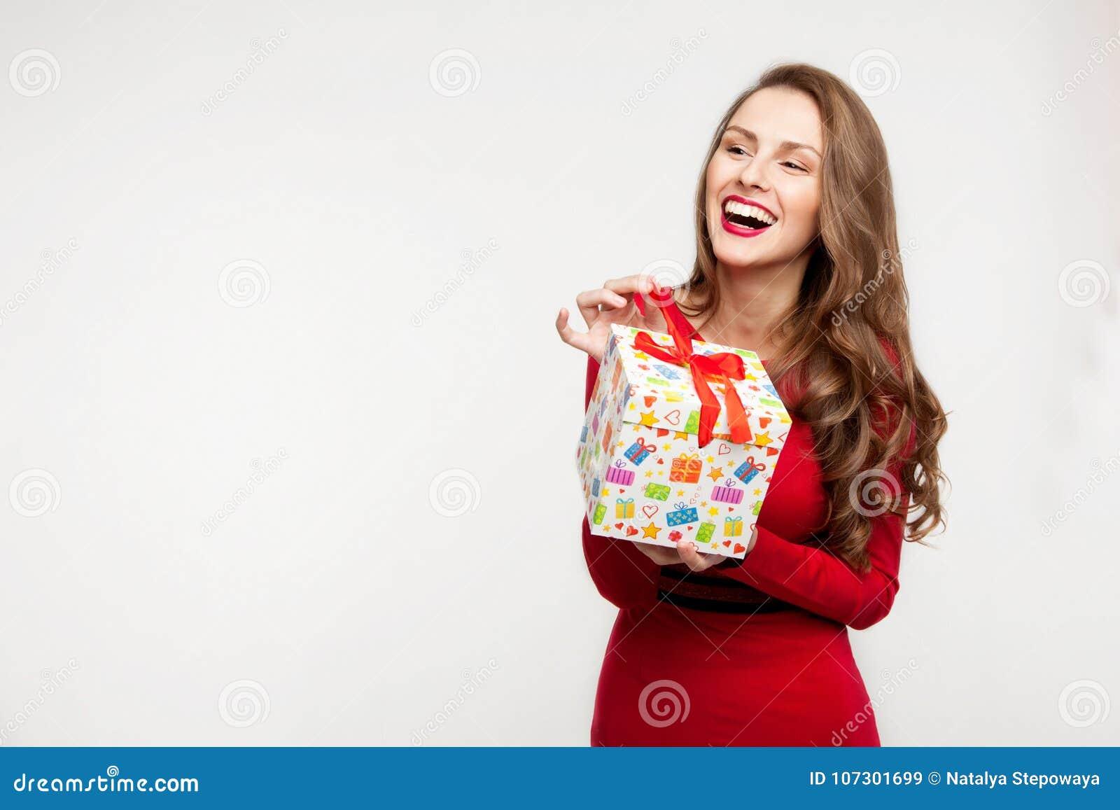 Brunettflickan rymmer en gåva och skratta för dag för valentin` s På vitbakgrund