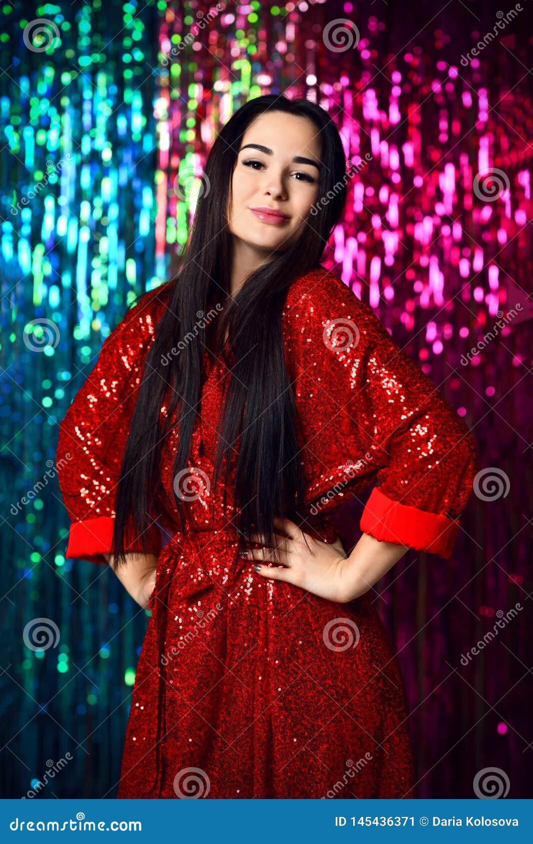Brunettkvinna som firar och att ha gyckel på partiet Stående av en lycklig le flicka i en stilfull glamorös skinande röd klä