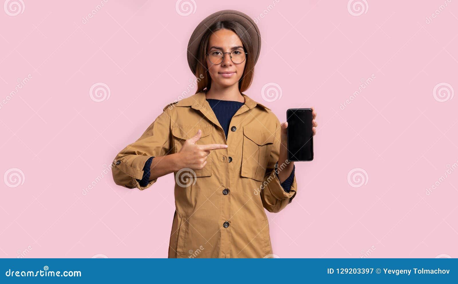 Brunettkvinna som pekar för att svärta smartphoneskärmen som isoleras över rosa bakgrund