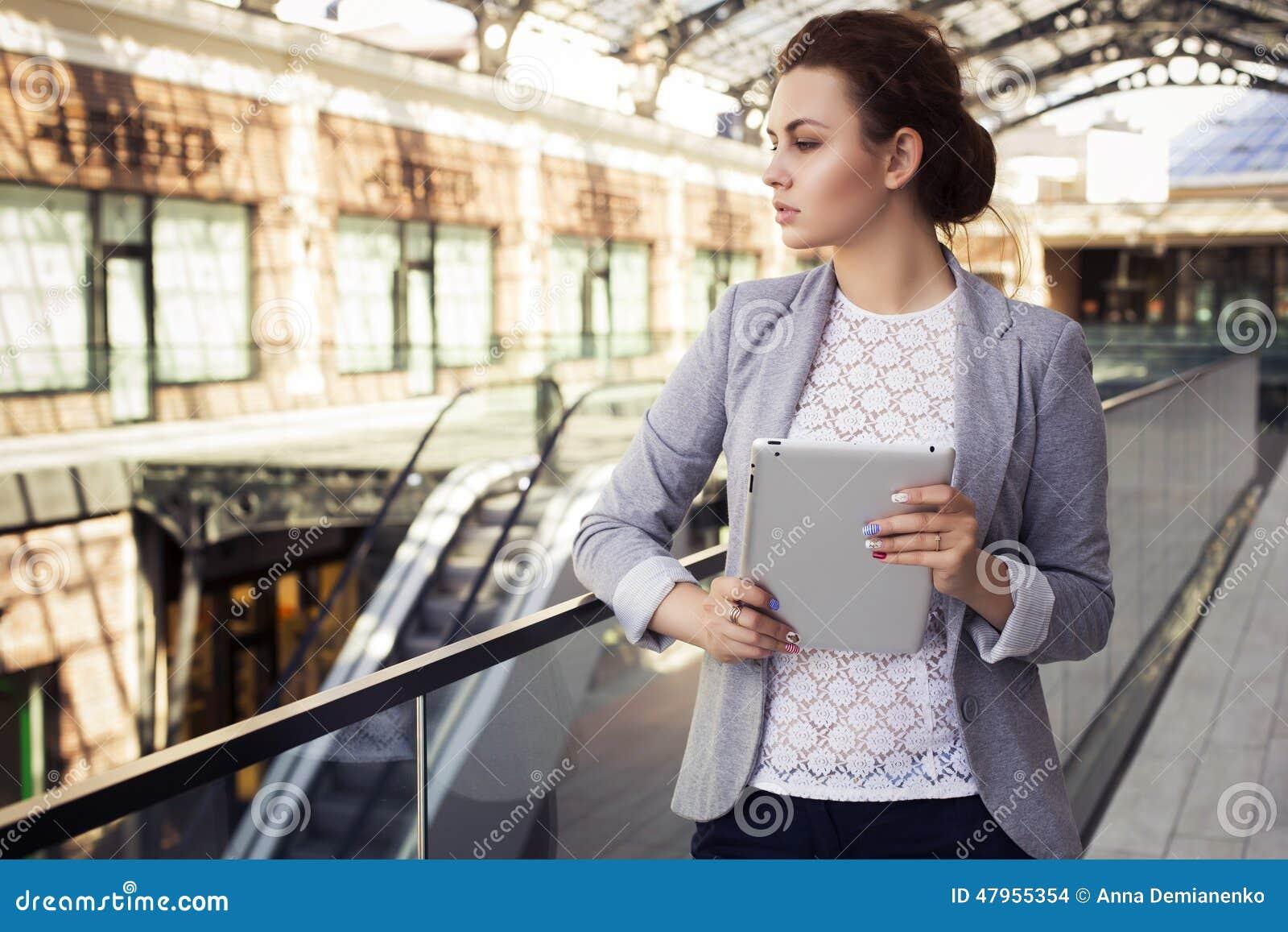 Brunettkvinnan i grå färger klår upp, mörk byxa och den vita blusen med minnestavlan utomhus kopiera avstånd