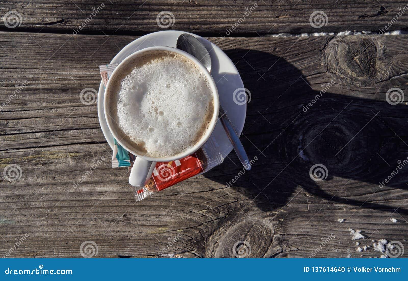 Brunnach Ski Resort, St Oswald, Carinthia, Österrike - Januari 20, 2019: Kopp kaffe som fångas på en gammal trätabell