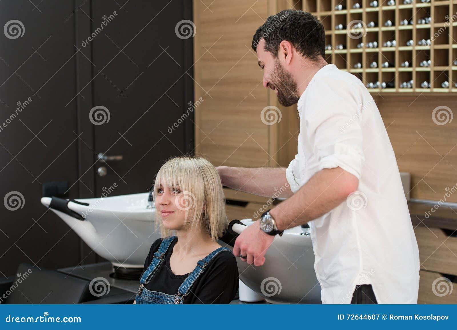 Bruno allegro che fa acconciatura per la ragazza bionda teenager nel salone di lavoro di parrucchiere