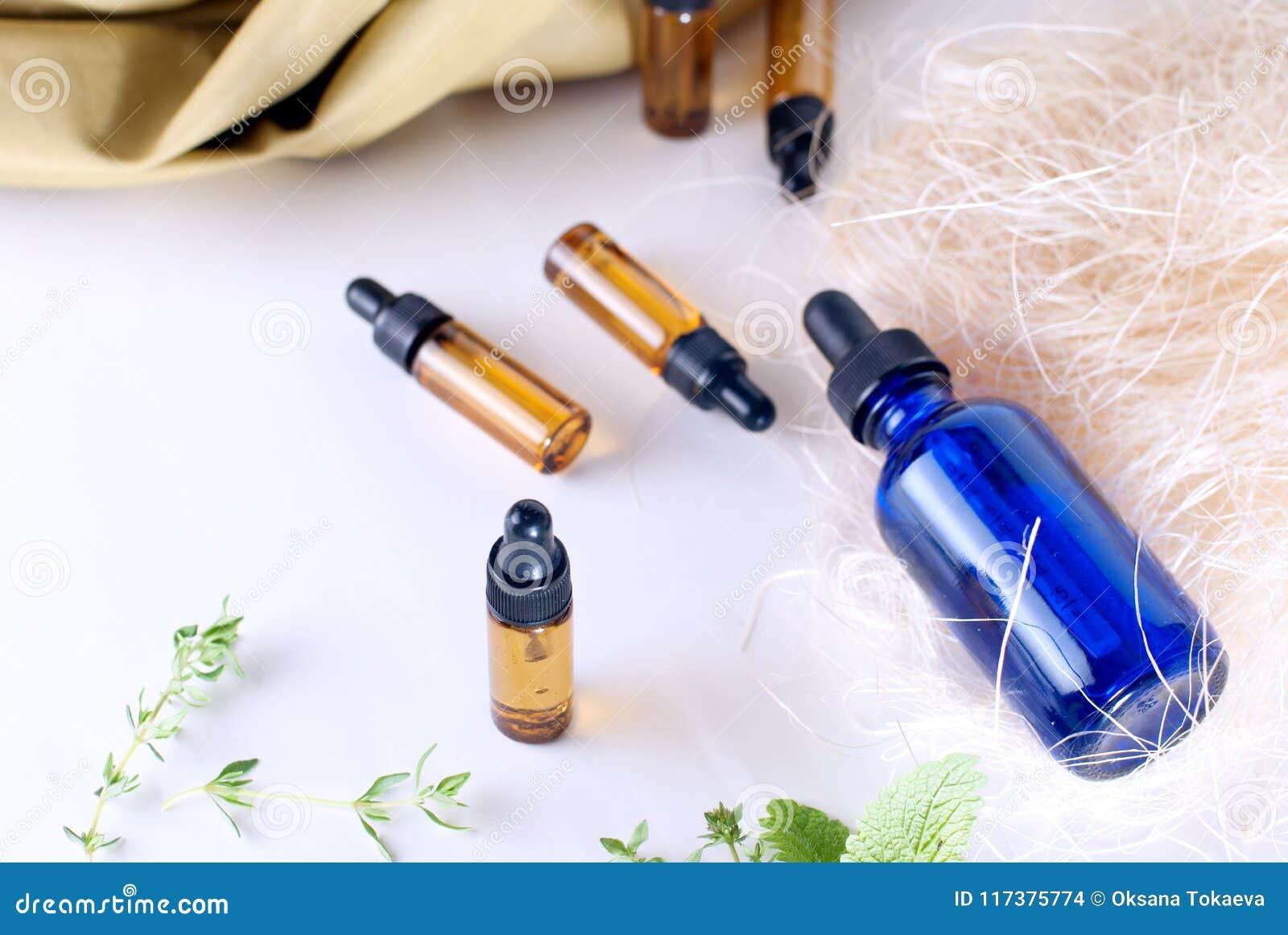Brunt- och blåttflaskor av nödvändig olja med ny timjan