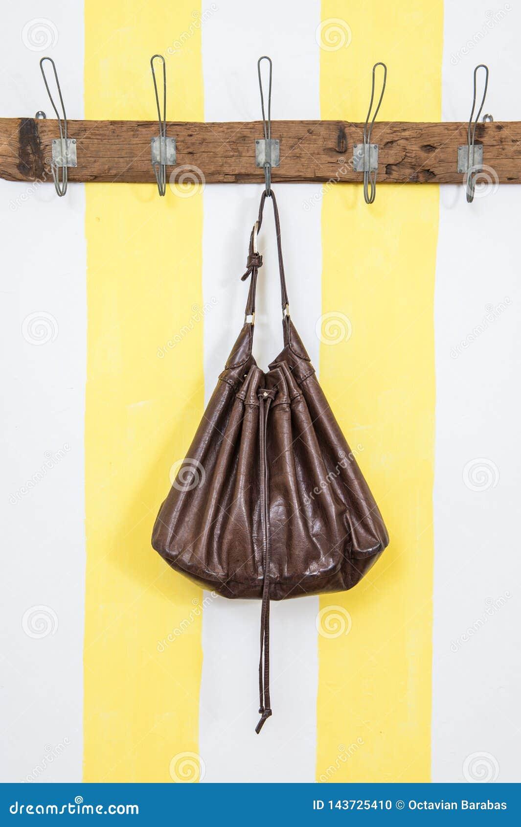 Brunt piskar handväskan på trägarderob