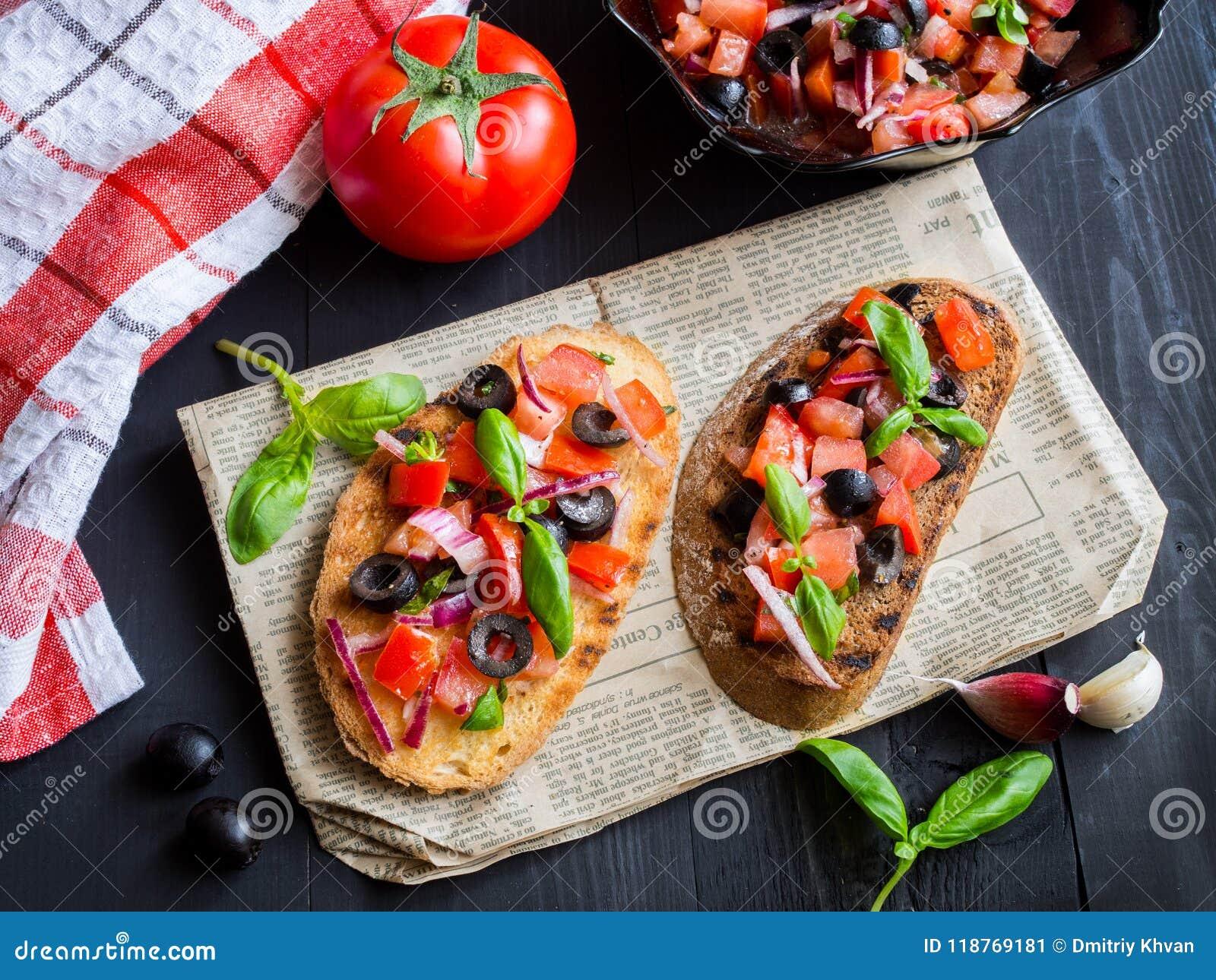 Bruschetta con el tomate y la albahaca en los tableros de madera negros