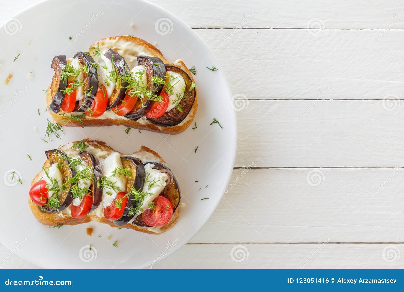 Bruschetta con las berenjenas fritas, los tomates frescos y el queso de la mozzarella en una placa en los tableros blancos