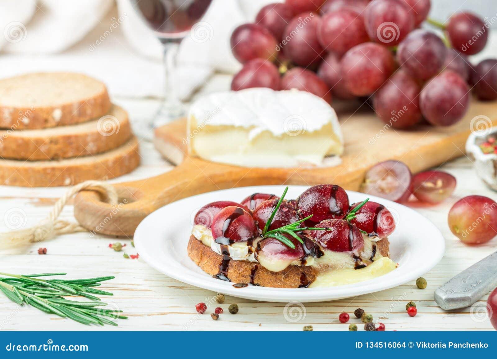 Bruschetta del queso del camembert o del brie con las uvas rojas, el romero y balsámico