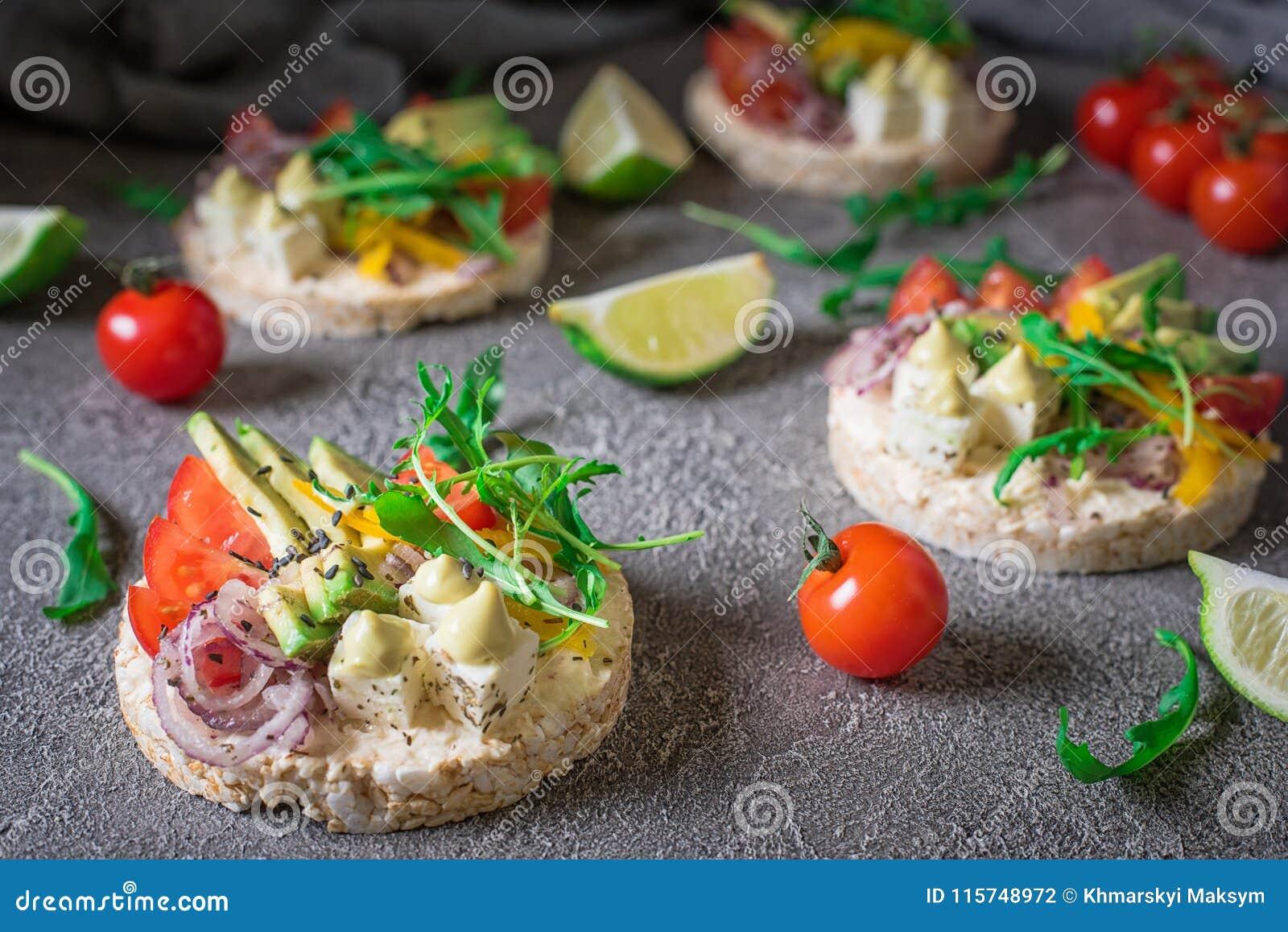 Bruschetta met tomaat, avocado, kruiden en arugula Rustieke achtergrond Hoogste mening