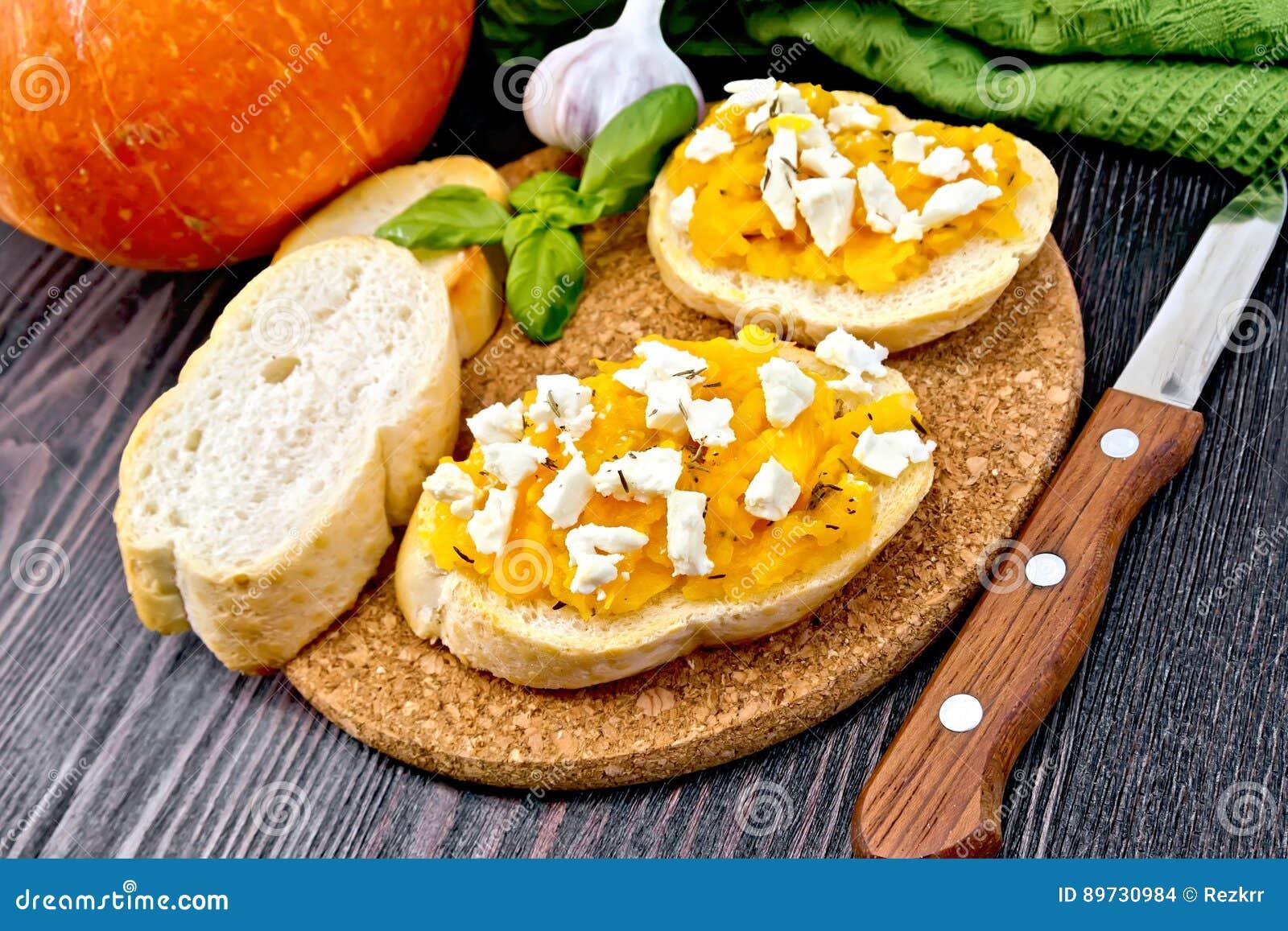 Bruschetta with pumpkin and feta on dark board