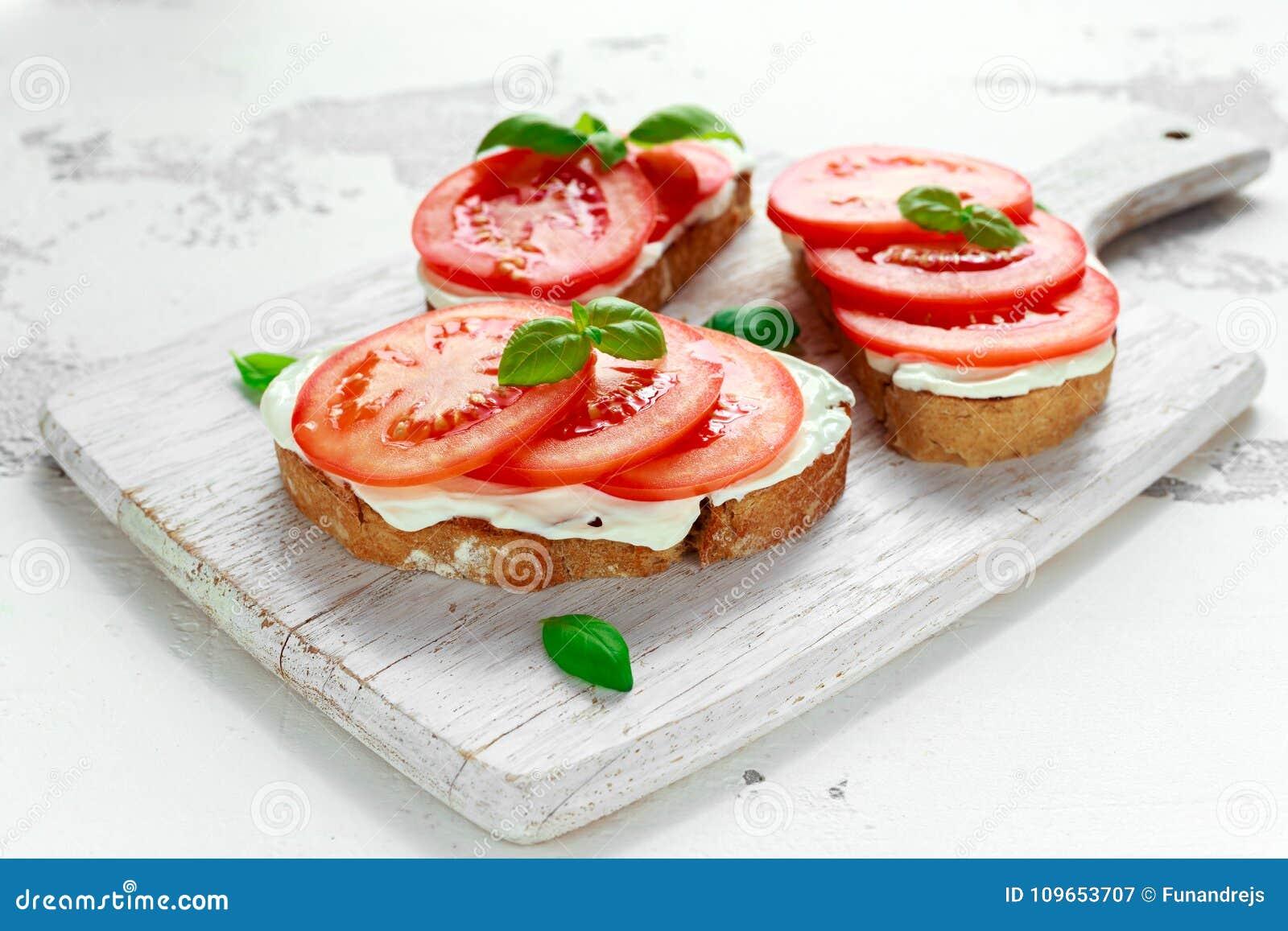 Bruschetta, Toast mit Weichkäse, Basilikum und Tomaten auf einem weißen hölzernen Brett Italienischer gesunder Snack, Lebensmitte