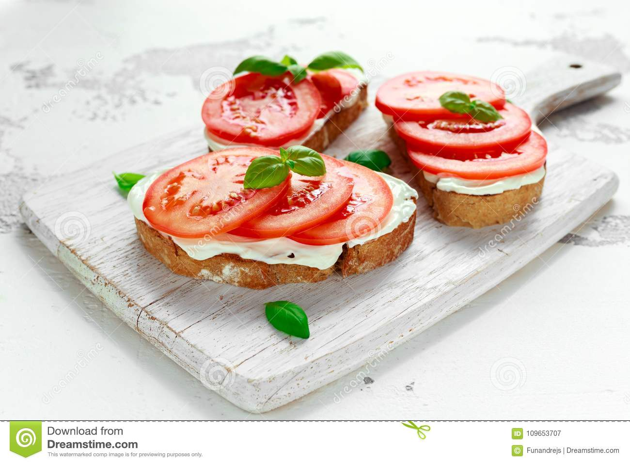 Bruschetta, toast with soft cheese, basil and tomatoes on a white wooden board. Italian healthy snack, food.