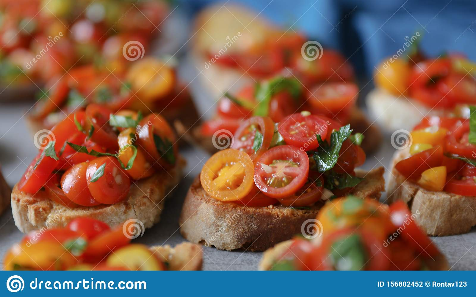 Bruschetta with tomatoes, basil and parsley, an Italian delicious savory appetizer.