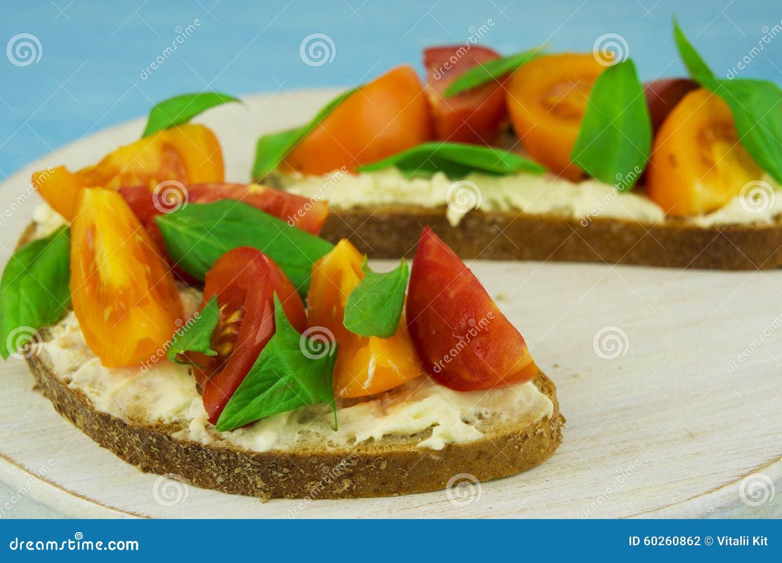 Bruschette avec le fromage à pâte molle, le basilic et les tomates-cerises sur un bois