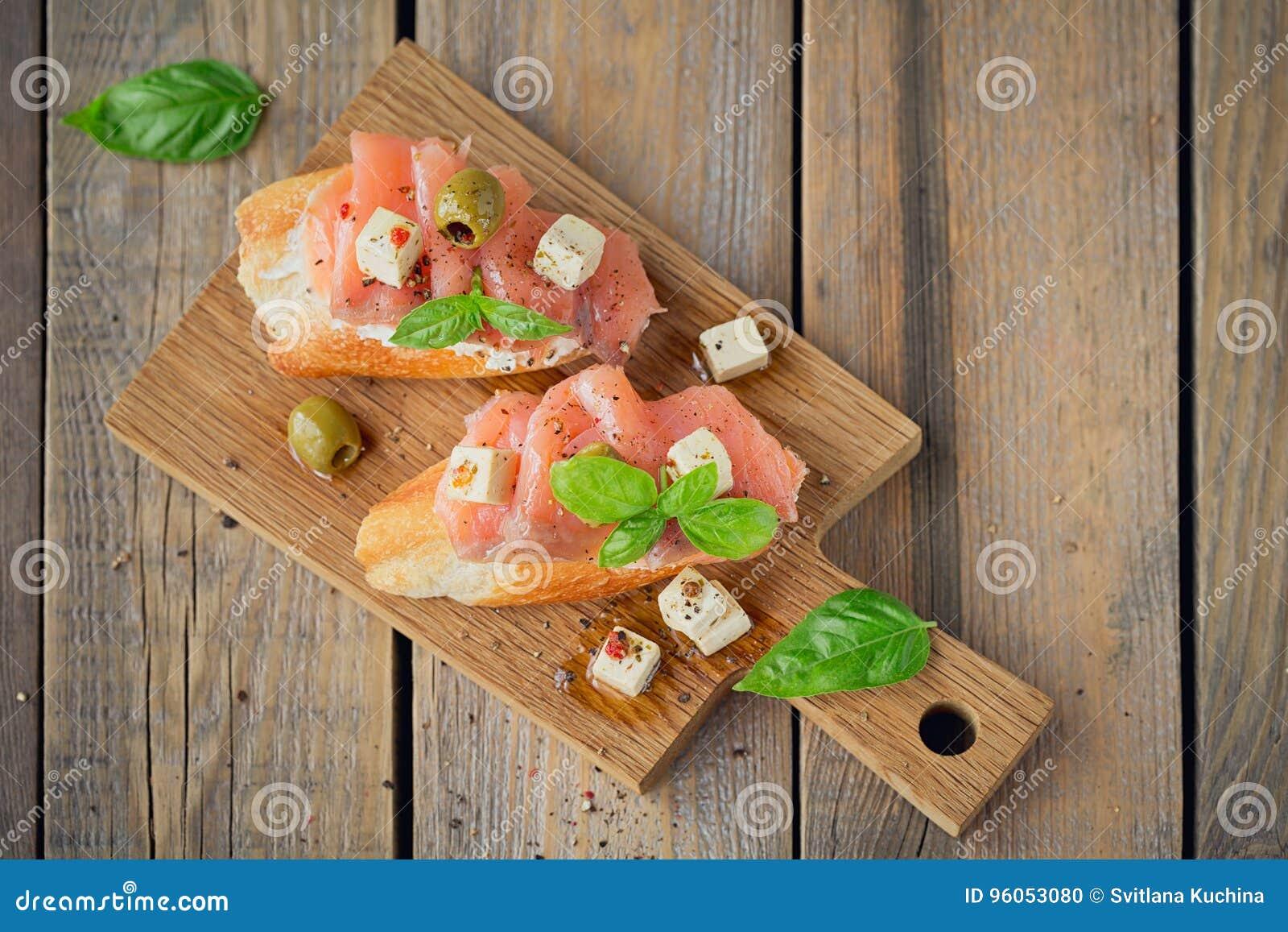 Bruschette avec le fromage de saumon et fondu fumé, les olives et l arugula