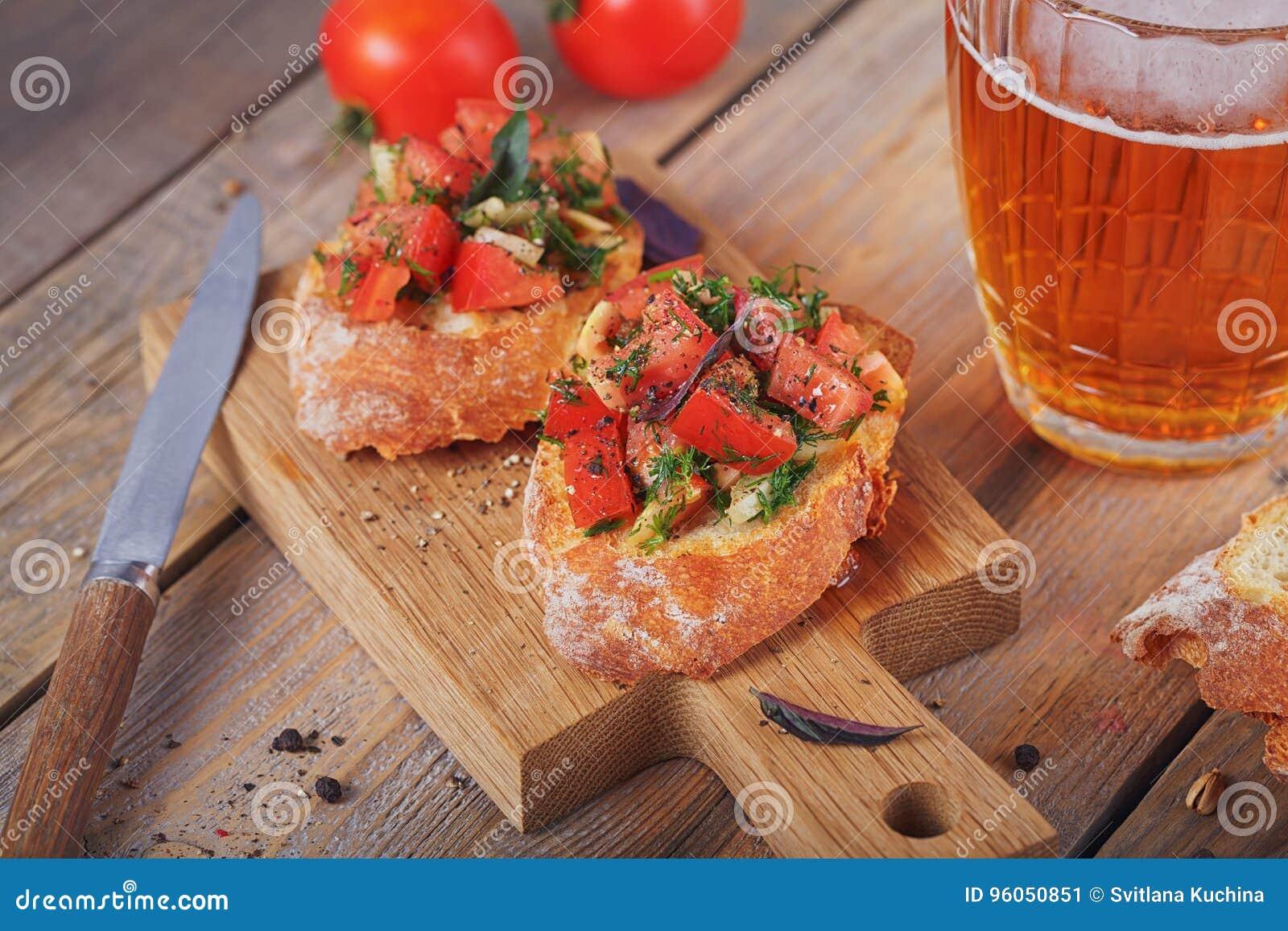 Bruschette avec les tomates, le basilic et les herbes coupés sur le cru grillé