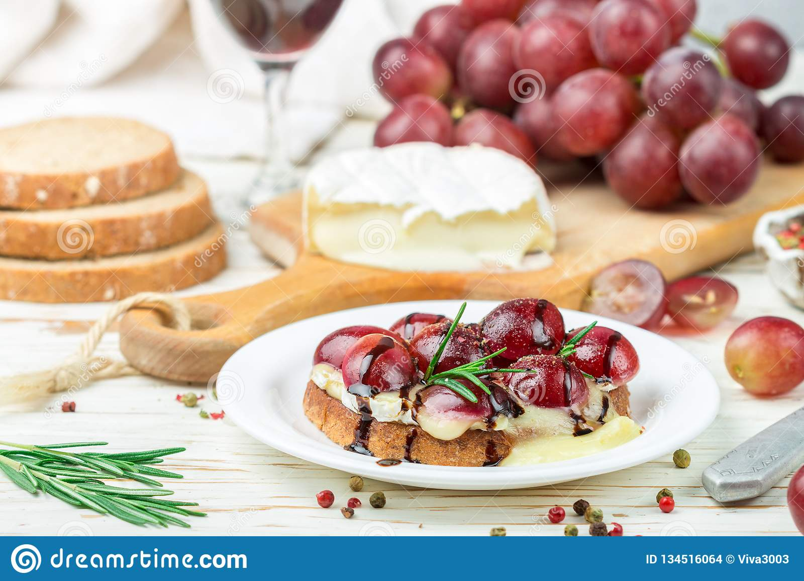 Bruschette de fromage de camembert ou de brie avec des raisins rouges, le romarin et balsamique