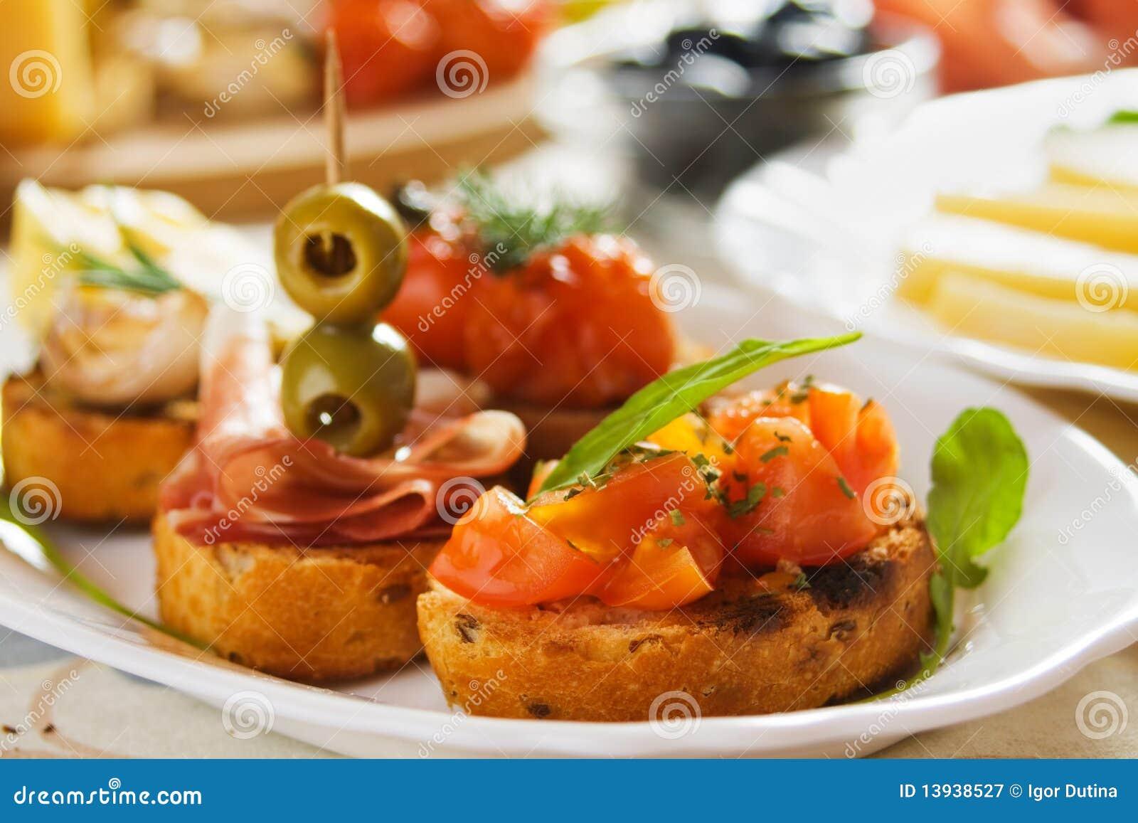 Bruschette with tomato, olives and prosciutto
