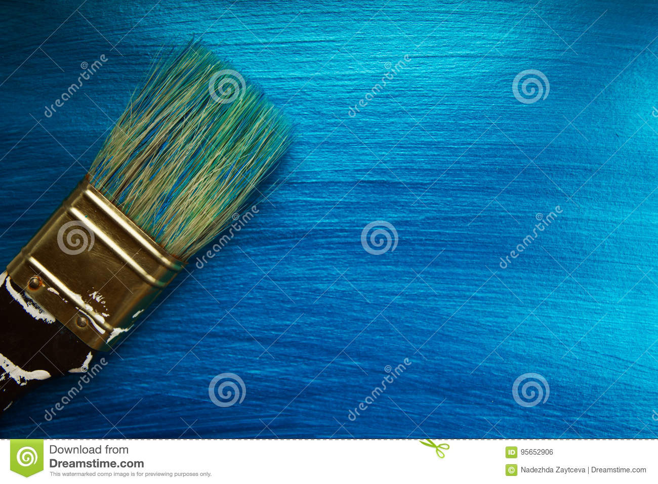 A brush on a blue nacreous color painted background.