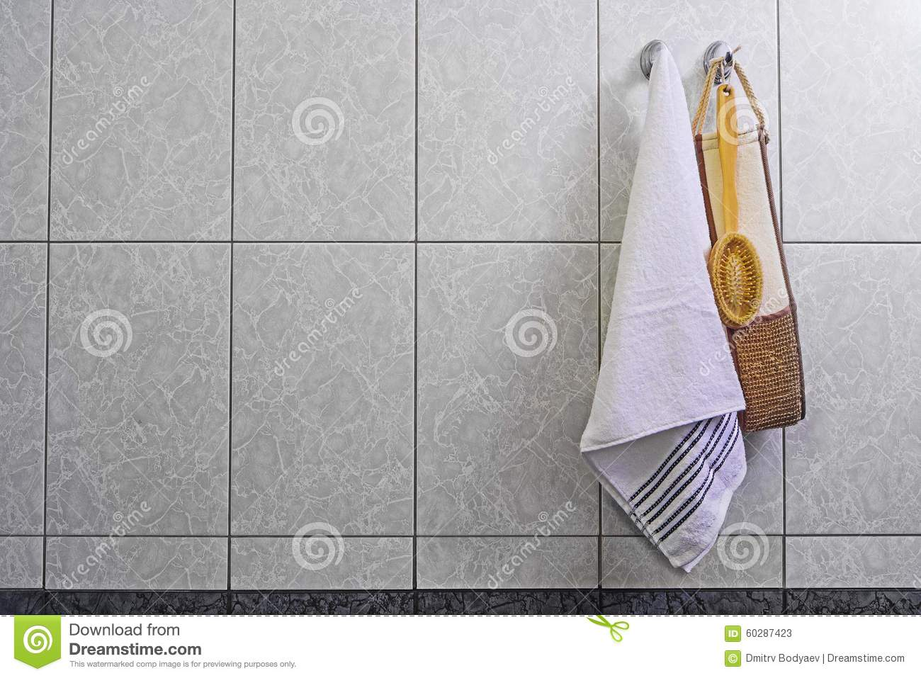 Brush washcloth and towel hanging on a hook in the bathroom, on