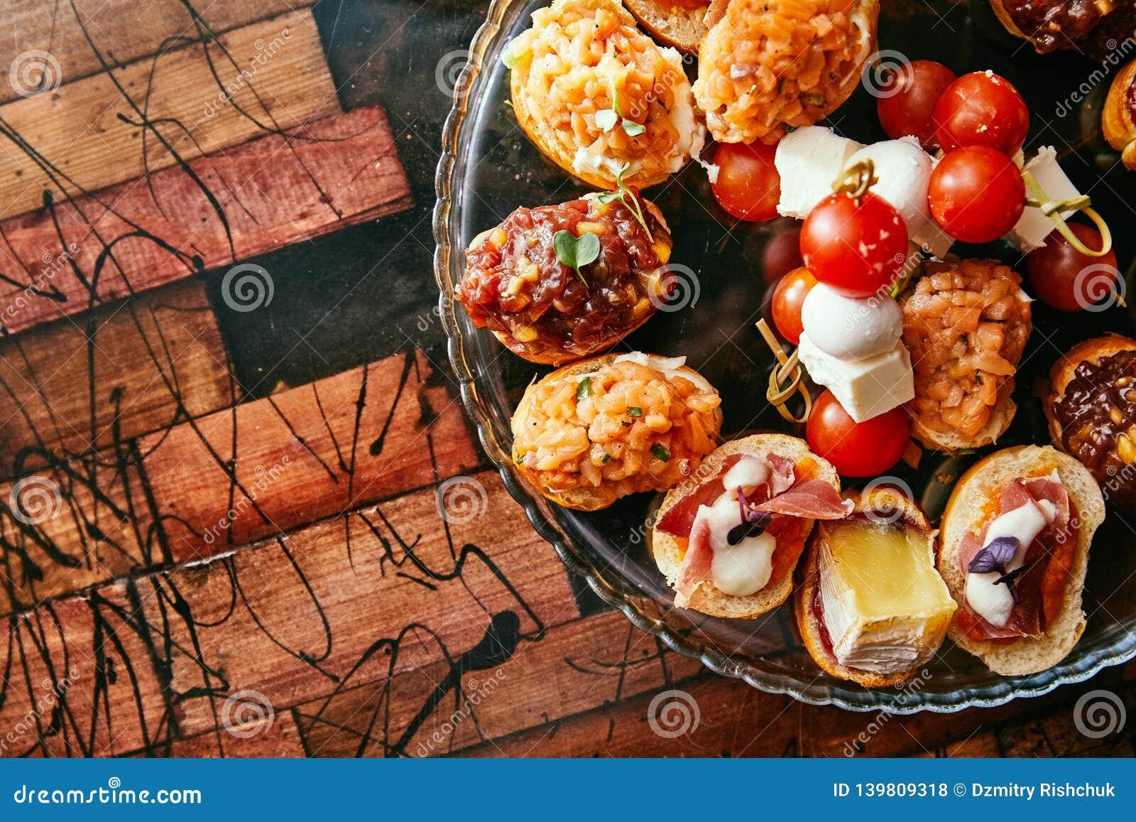 Brushetta o tapas españoles tradicionales Bocados italianos de los antipasti de los aperitivos fijados con el vino La visión supe