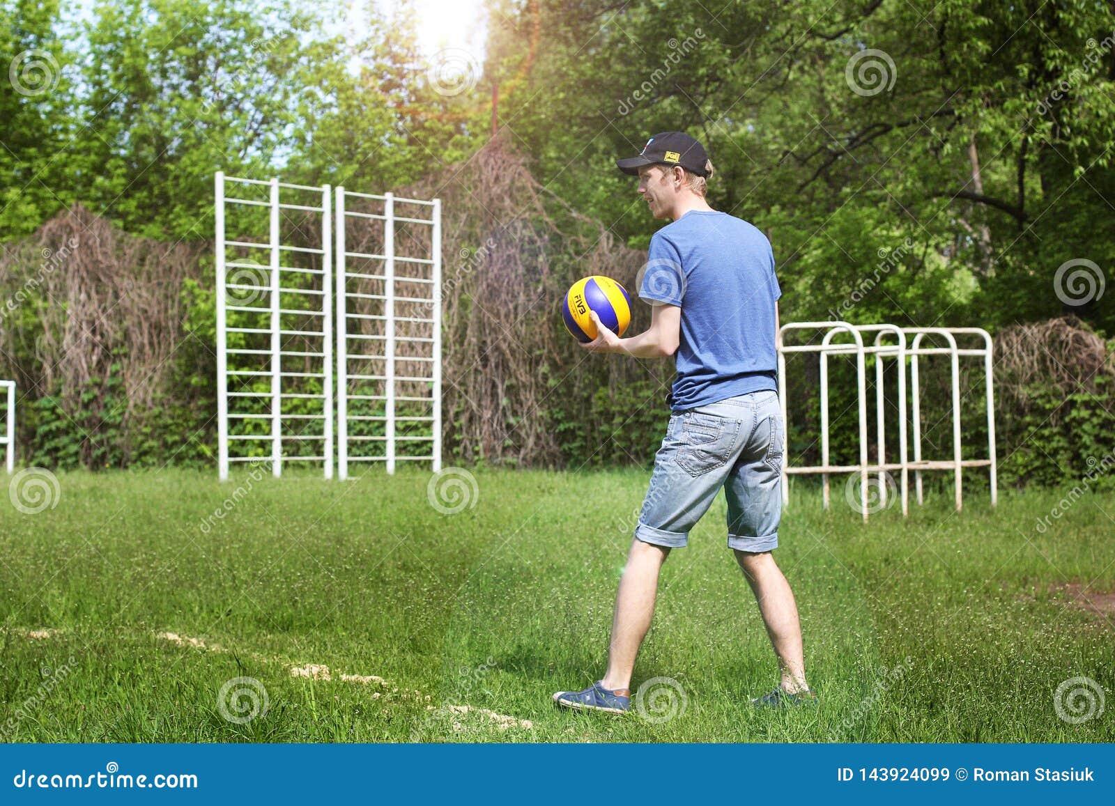 Brusilov Ukraina, Maj, - 9, 2018: Sportowy facet bawić się siatkówkę w lecie