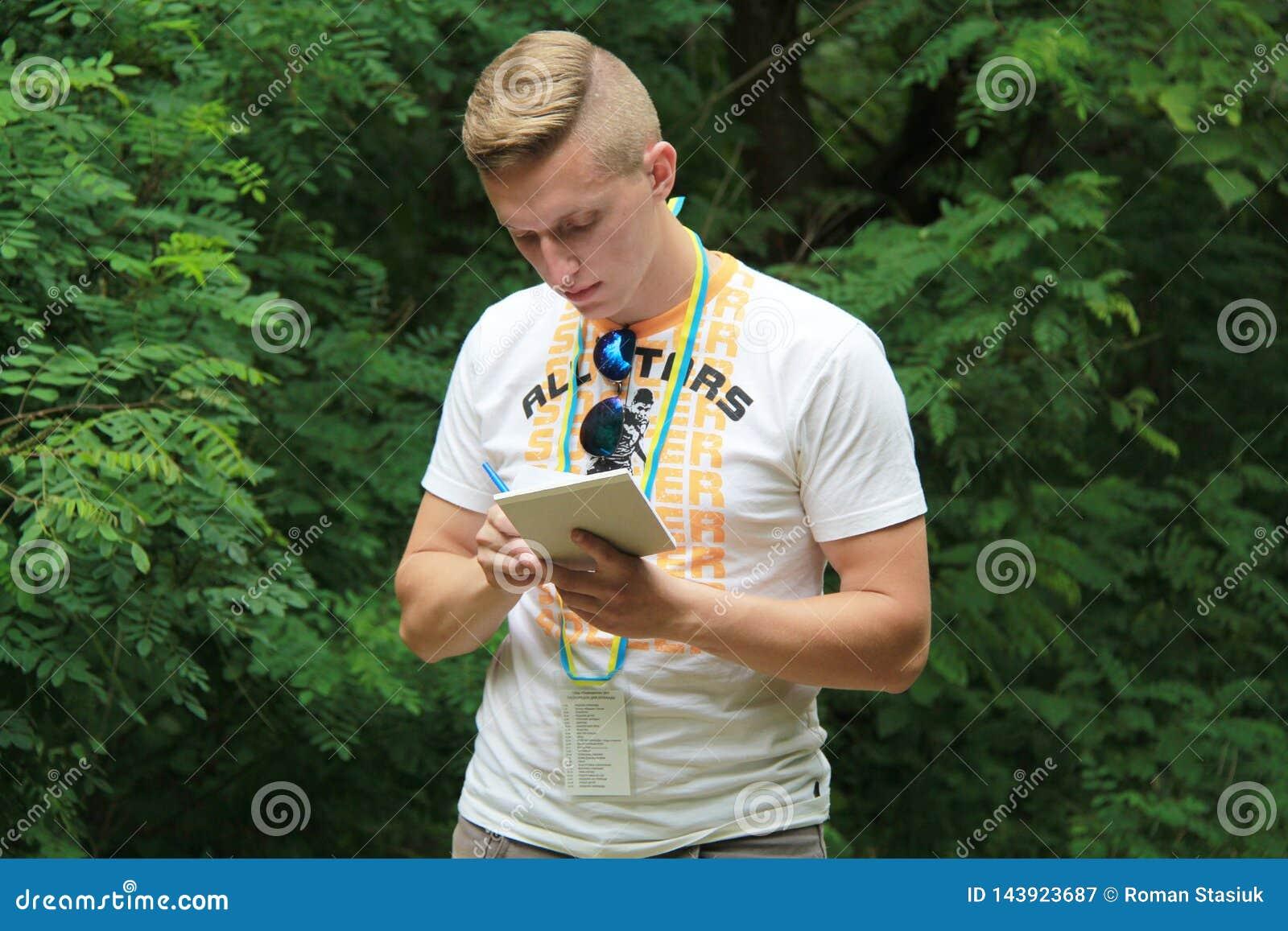Brusilov, Ukraine - 17. Juli 2017: Ein Sportkerl in einem weißen T-Shirt notiert die Ergebnisse der Tests Junger Trainer