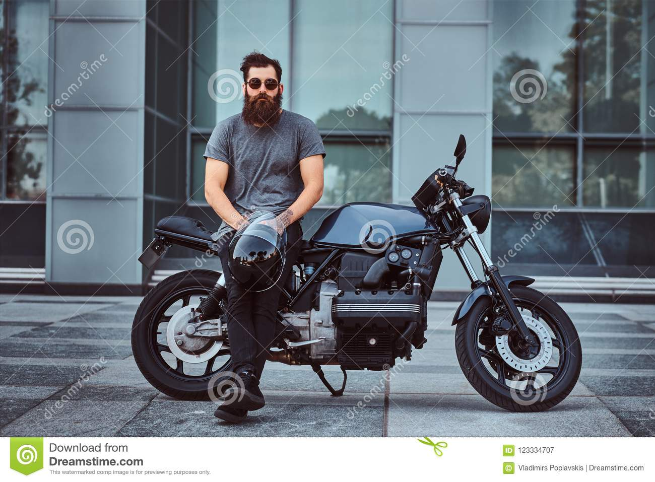 Brutal bearded male in a gray t-shirt and black pants holds a helmet sitting on his custom-made retro motorcycle against