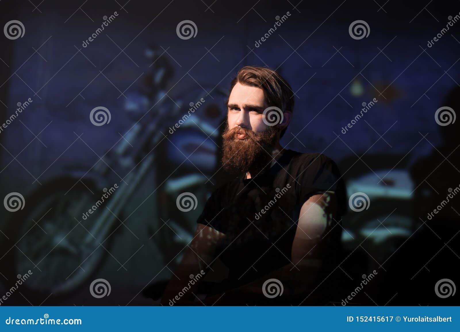 Brutal bearded man biker sitting in a chair.
