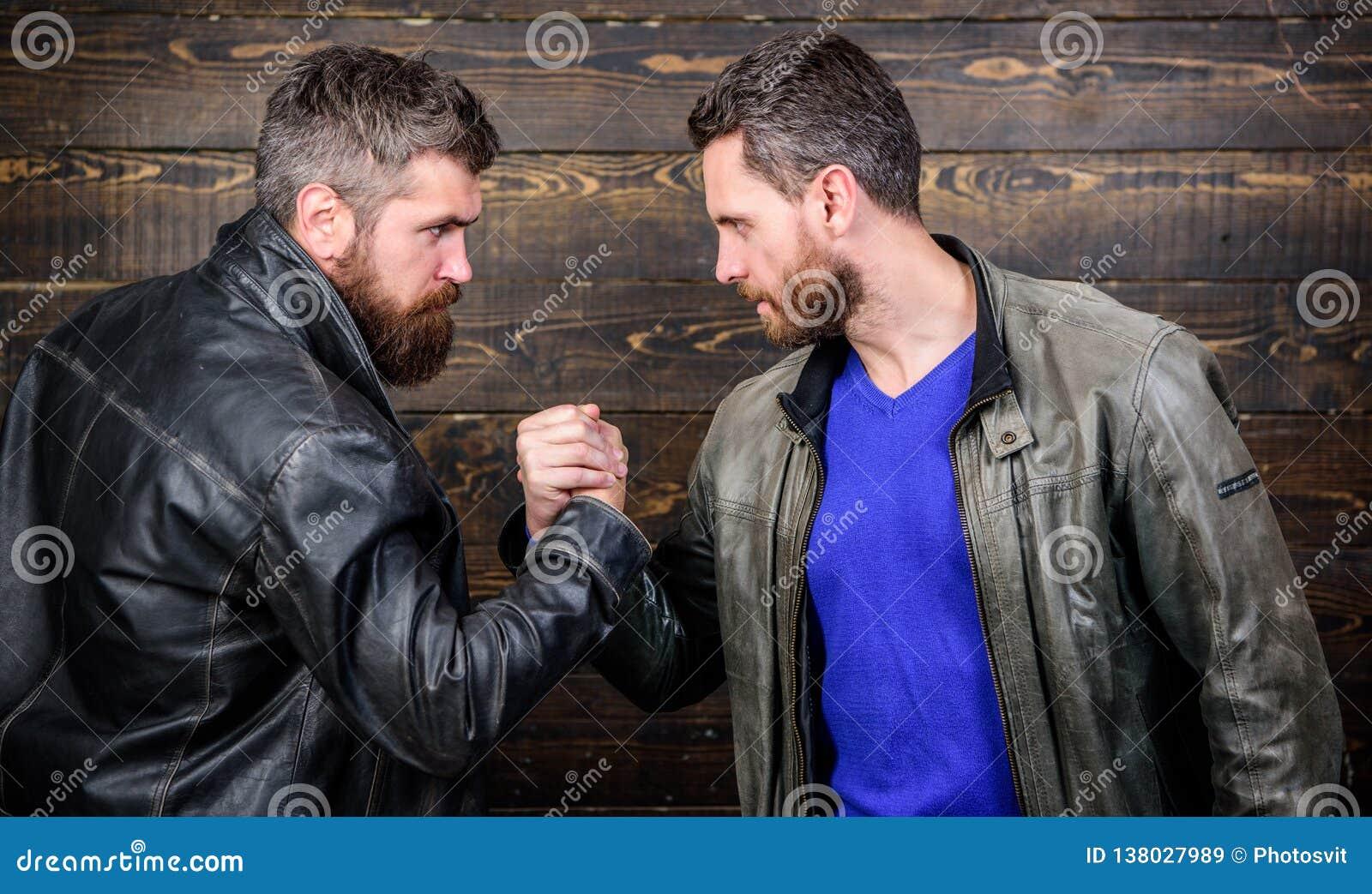 Brutal bearded men wear leather jackets shaking hands. Strong handshake. Friendship of brutal guys. Handshake symbol of