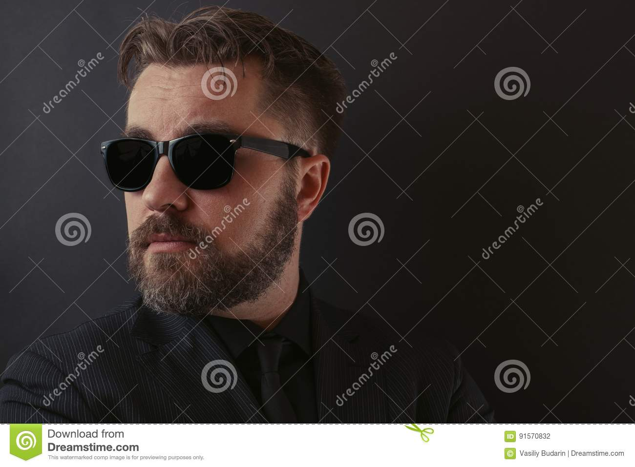 A brutal man with a beard and a stylish hairdo in a black suit and sunglasses